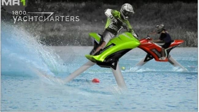 Photograph of a person wearing a helmet and riding a hydrofoil water bike on a lake. The bike is lime green. The helmet is silver. The guy looks like he is riding a motorcycle. There is a big wave kicking up behind him.  There is another person riding on a red one in the background.