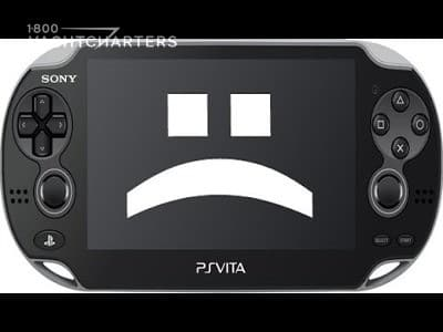 Photograph of the Sony PlayStation Vira with a sad face on the screen.  The face appears as 2 dots above a frowning end parentheses character. The PlayStation Vita is black, and the sad face is white.