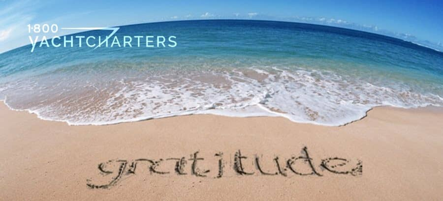 Photo of a sandy beach with the word, gratitude, written in the sand. The waves are approaching the word. White waves, then teal water, then dark blue water, with an island in the background. The photo was taken iwith a round lens.