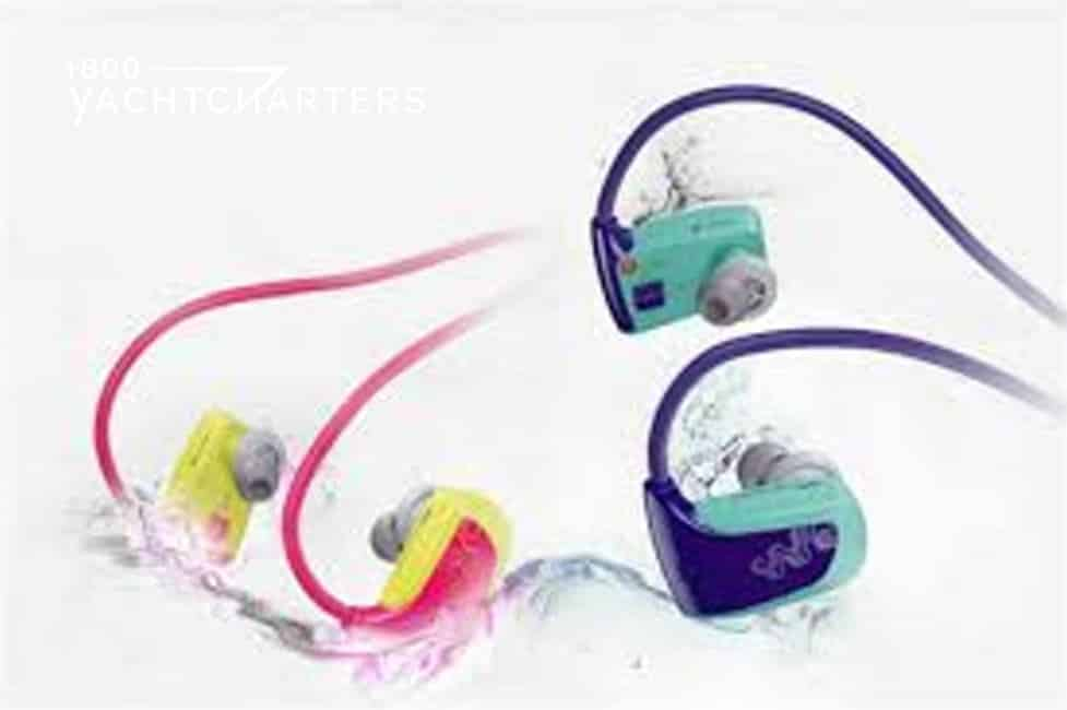 Photo of two sets of headphones floating on a wave. The left side earbuds are pink and yellow. The right side earbuds are navy blue and mint green