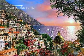 Photograph of Positano in Italy. Photo taken from up on the hill.  The mountain to the left is covered in multicolored houses that are on a slant overlooking the ocean.  The bay is filled with sailboats and motoryachts at anchor. There is a pink cloud in the background, as if the photo was taken at sunset.