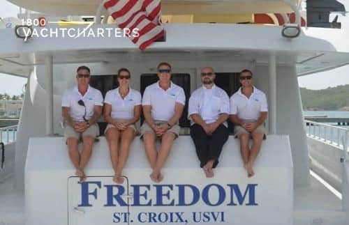 Freedom yacht crew sitting on the back of the boat. They are hanging their legs down over the name of the boat.