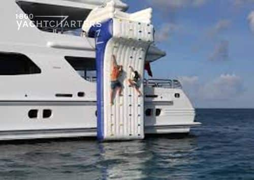 Inflatable climbing wall on the side of a white yacht. The wall is white with blue edges, and the handholds are red and blue. There are 2 people climbing up the wall.