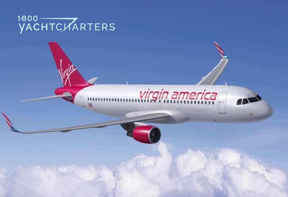 Aerial profile photograph of a white jet flying over puppy white clouds. The sky is bright blue. The plane is white with red letters reading, Virgin America. The plane is flying toward the right side of the photograph. The tail of the plane is red, as are the wing tips and engines underneath the plane. The tail reads the word, Virgin, in white script lettering.