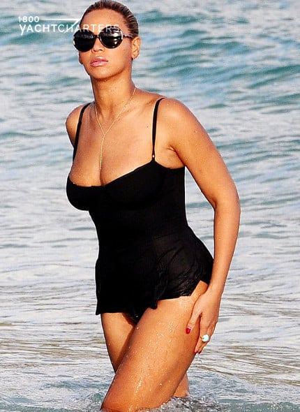 Photograph of Beyonce in the ocean in St. Barts. She is wearing a black one-piece modest Norma Kamali swimsuit. with spaghetti straps. She is wearing black sunglasses, has her hair back, and is no expression on her face