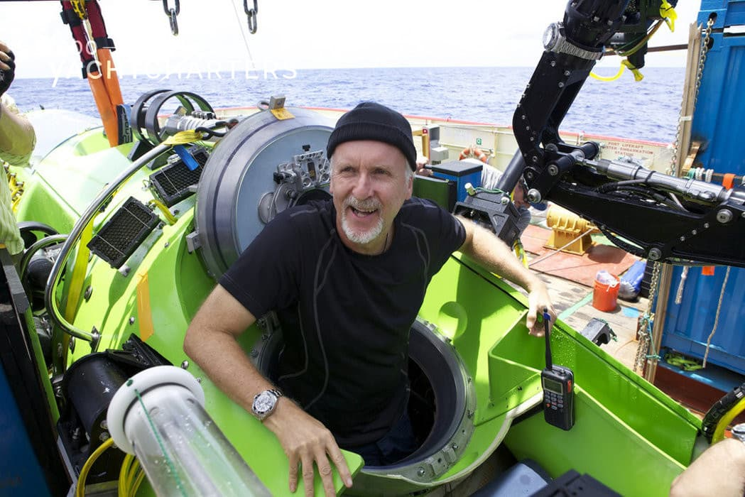 Photograph of James Carmeron sitting in a small green submarine that is sitting on a ship. He has a huge open smile.