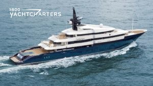 Aerial view of motoryacht with blue hull and white superstructure underway