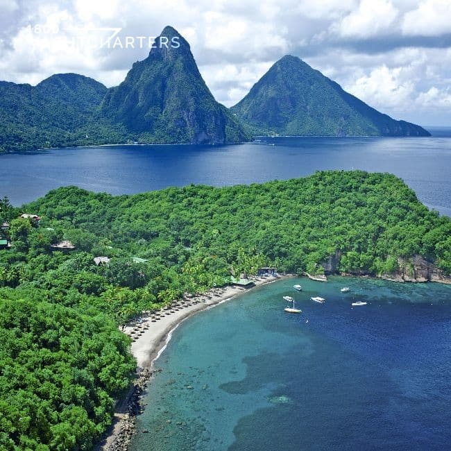 Aerial photograph of a cove on the island of St. Lucia in the Caribbean. The cove has about 5 boats anchored there.