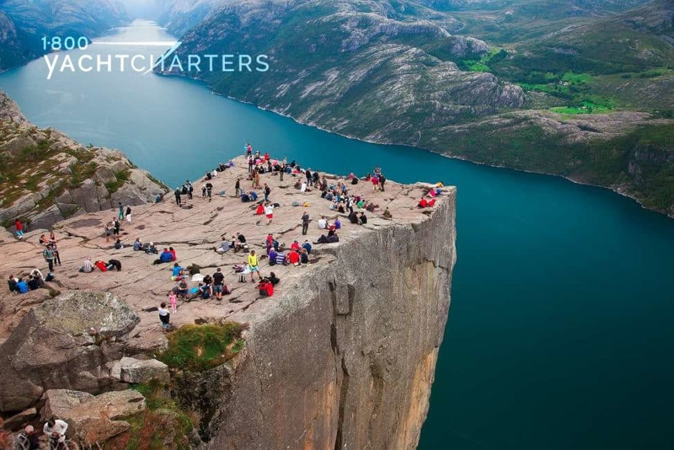Aerial photo of Pulpit Rock in Norway. Multiple people sitting on top of the giant rock that overlooks water far below