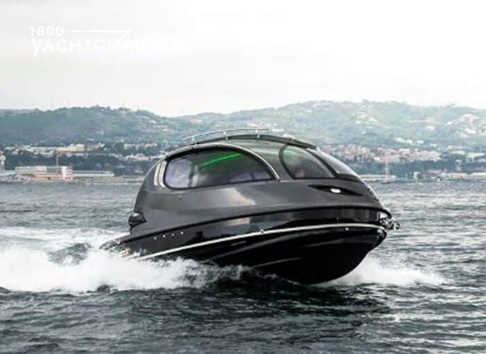 Photograph of a black Lazzarini jet capsule underway. It looks like a pod on the water. It is headed toward the right side of the photograph. There are mountains in the background. It is kicking up a wake.