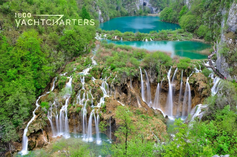 Aerial photograph of mountains, green trees, turquoise water, and waterfalls flowing from the lakes. Perfect Croatia yacht charter destination