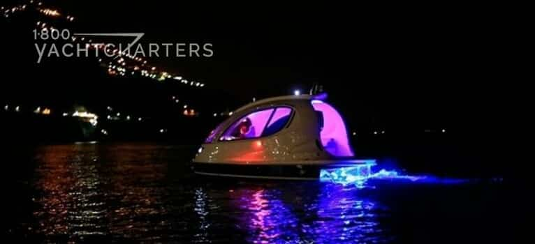 Photograph of a jet capsule on the water at night. It is headed toward the left side of the photograph. The interior lights are purple, and the underwater lights are blue.