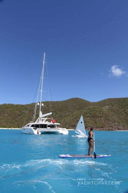 sailing yacht catamaran charter and stand up paddleboard rider