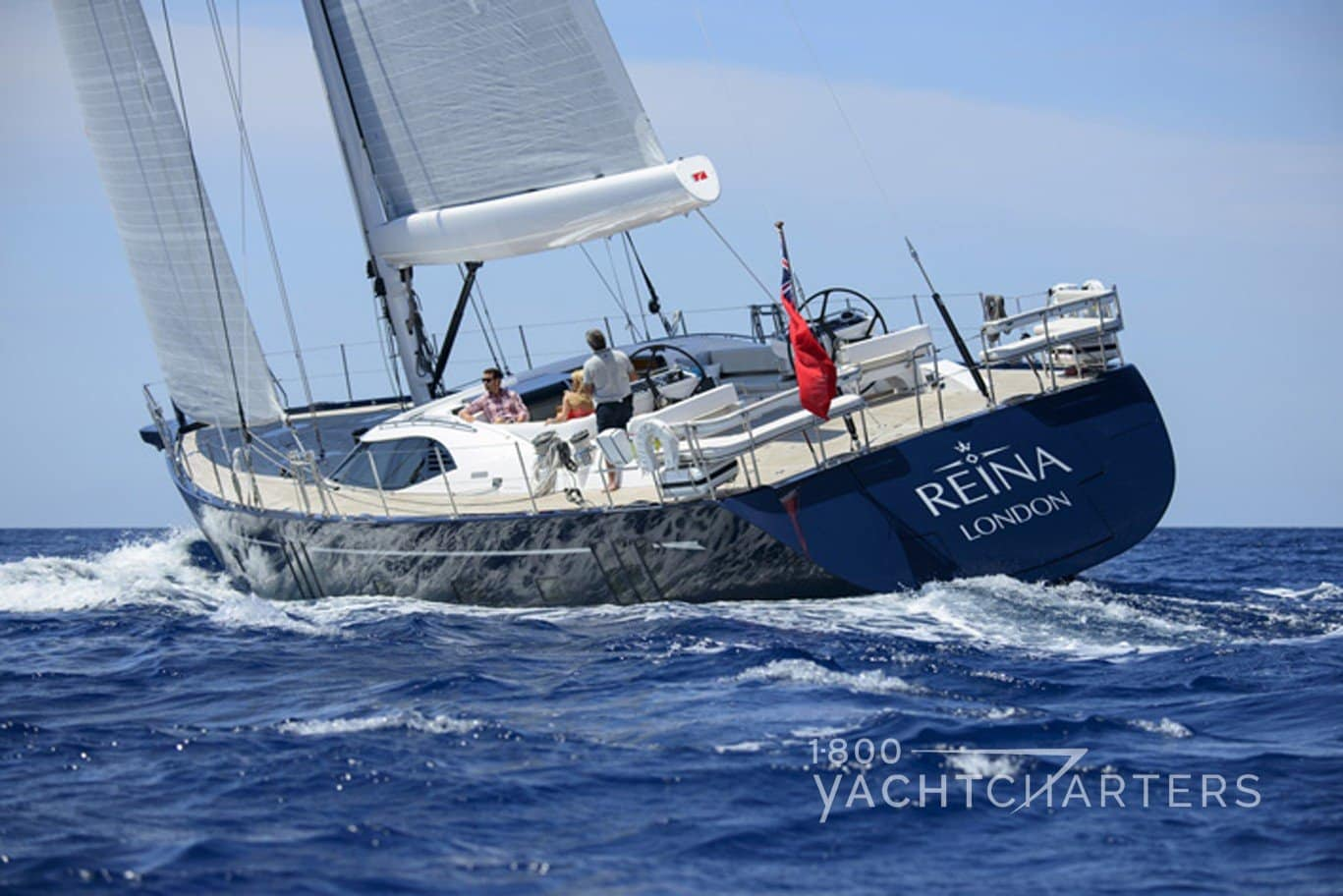REINA Oyster sailing yacht blue hull and wooden deck running - view from back