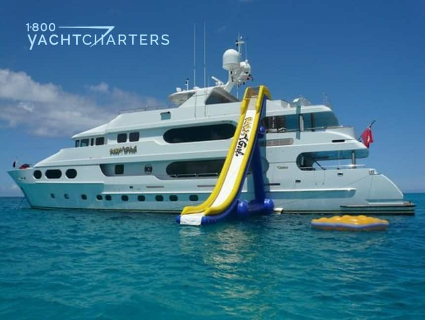 Yellow and blue inflatable slide from the top deck of the anchored motor yacht PARTY GIRL