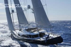 Back of sailboat yacht under sail.  Boat has black hull, white superstructure, and white sails.