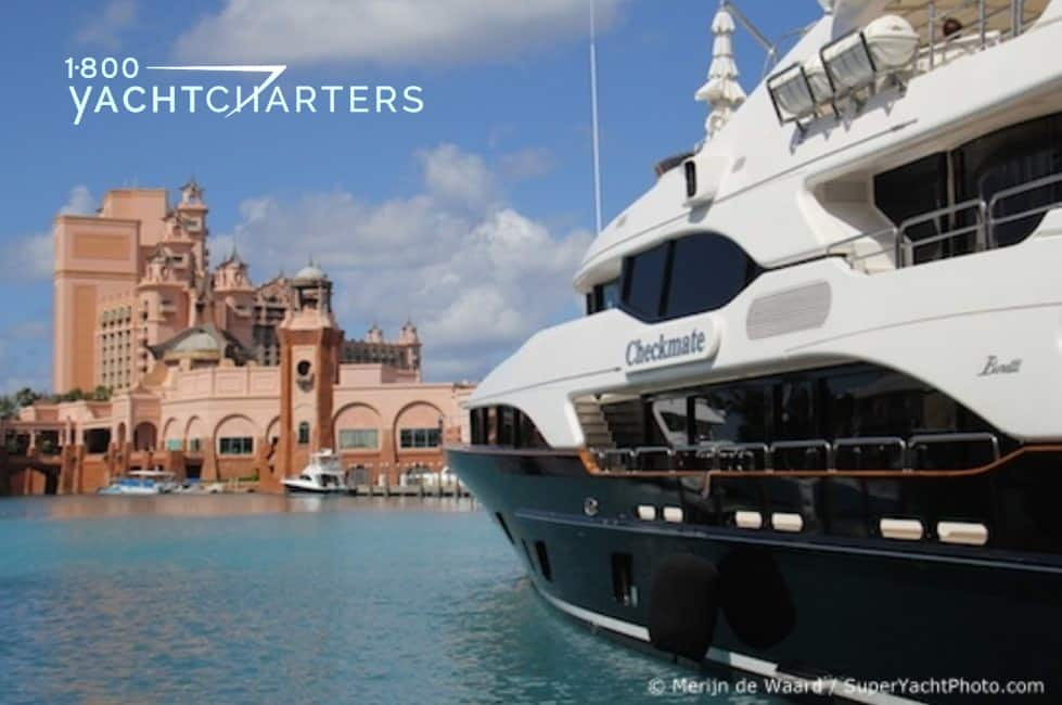 Photograph of a dark hulled yacht on the right side of the frame, and Atlantis Resort in the Bahamas on the left