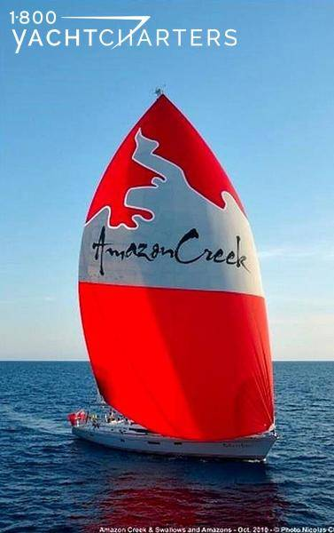 AMAZONCREEK under sail with giant red and white sail that says AMAZONCREEK