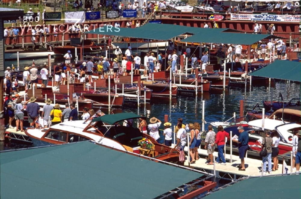 Aerial view of marina full of wooden antique boats and people on the docks looking at the boats