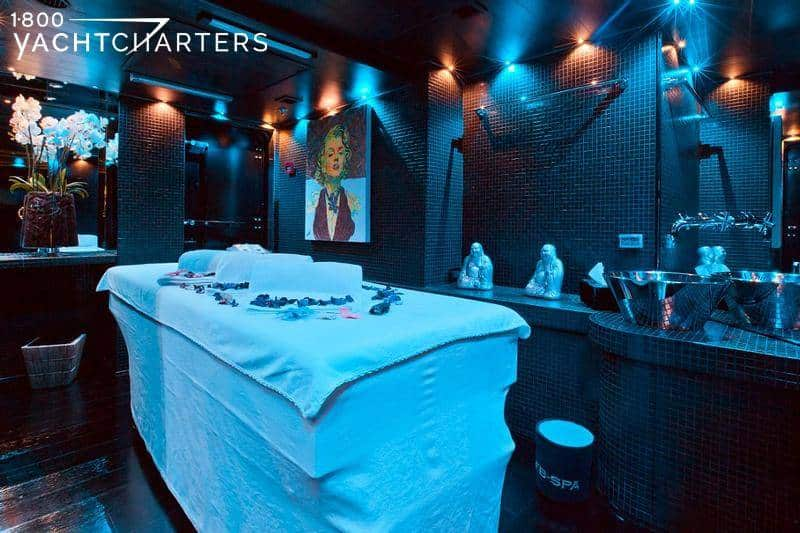 Massage room of motoryacht Force Blue featuring massage table surrounded by aromatherapy candles, fresh flowers, and zen touches in a softly lit room with Marilyn Monroe portrait