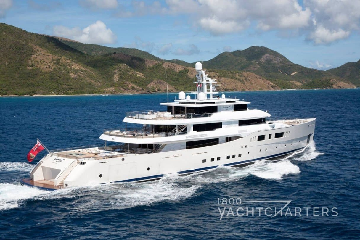 Aerial profile photograph of motoryacht Nautilus running. She is heading toward the top right side of the photograph. There is a mountain in the background. The water is deep blue