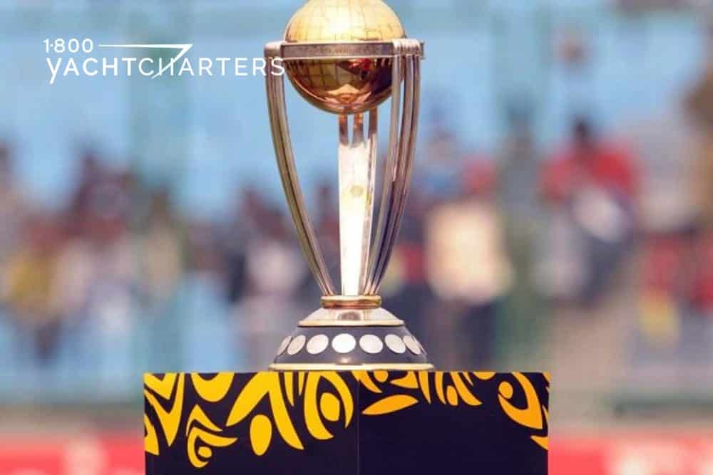 ICC Cricket World Cup Trophy on a table with black tablecloth that has ICC cricket world cup logo on it