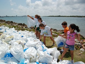 Kids cleaning up the shoreline of plastic by Luis Espinosa