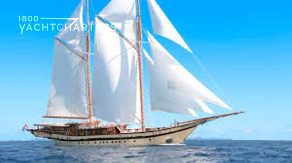 Lamima sailboat. Photo of the wooden sailboat anchored and facing to the right. Clear blue sky behind. Anchored on calm water. Yellow hull. Multiple large and small sails. Very elegant sailboat with a long bow sprit (pointed tip to the sailboat)