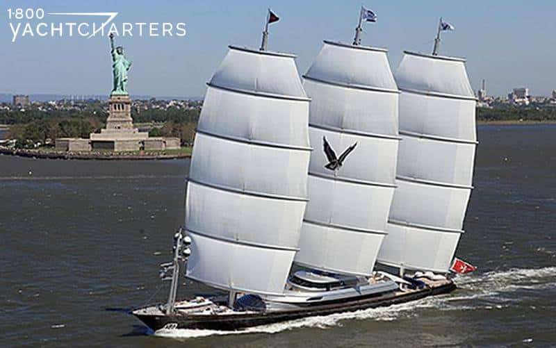 Aerial photo of 3-masted sailboat, Maltese Falcon, underway. Center sail has a black flying falcon logo on it. Hull of yacht is dark against waves lapping at side of yacht. The statue of liberty and Ellis Island is in the backround
