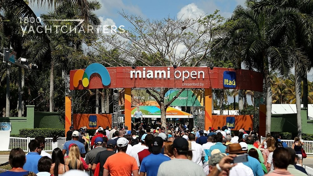 Crowd of people walking underneath a square arch that reads Miami Open