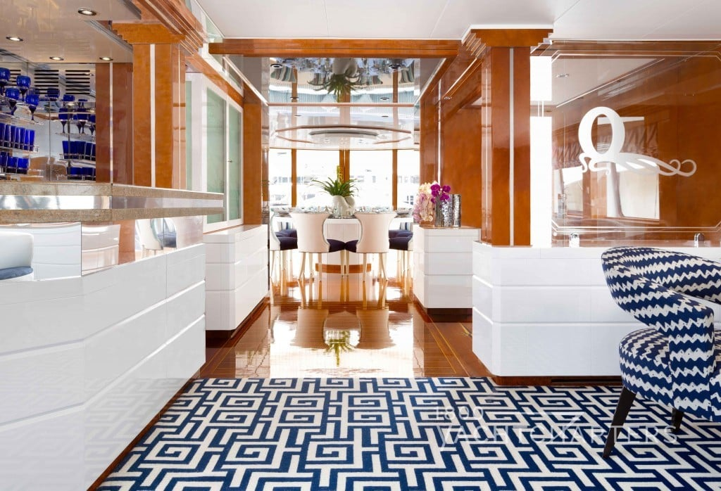 OCTOPUSSY main salon and dining salon entrance with blue and white geometric carpeting, light wood walls, and white furniture