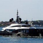Profile of yacht entering harbor - reflective dark hull brightly shining