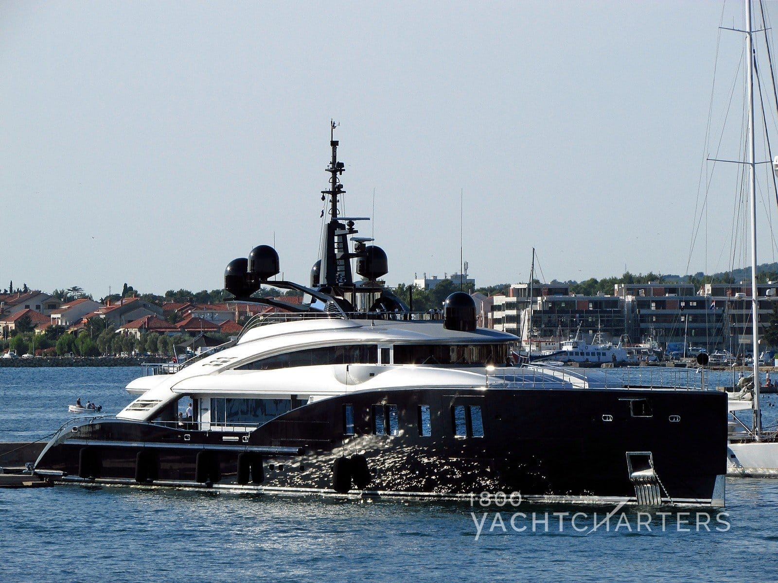 Profile of yacht entering harbor - reflective dark hull brightly shining