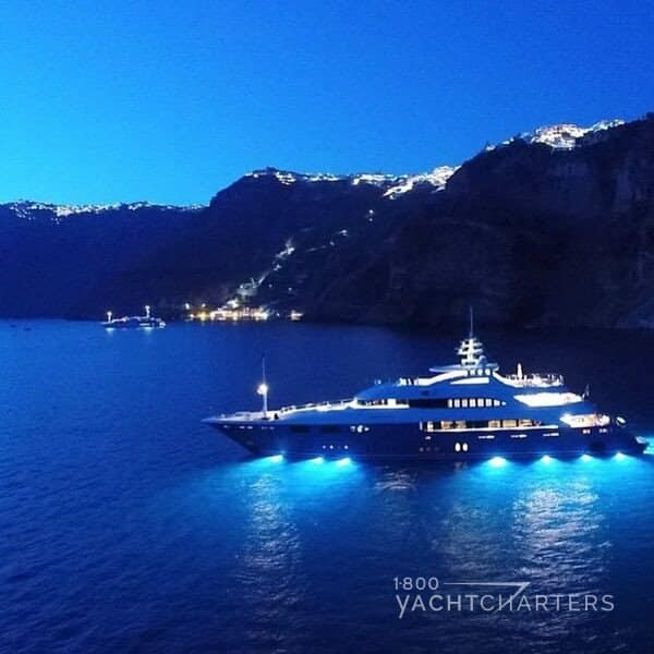 O'Neiro motoryacht anchored at night in a cove in Santorini - underwater lights below yacht