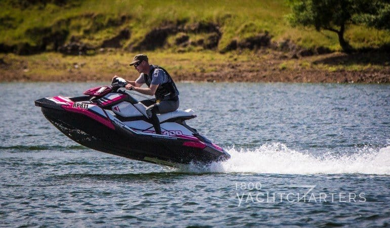 Sea-Doo Spark personal watercraft with man riding and nose of waverunner in the air - fast