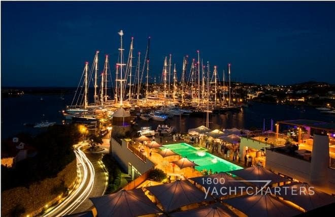 Aerial night view of Porto Cervo yacht club docks for night entertainment after sailboat race - many sailboat masts - lit pool
