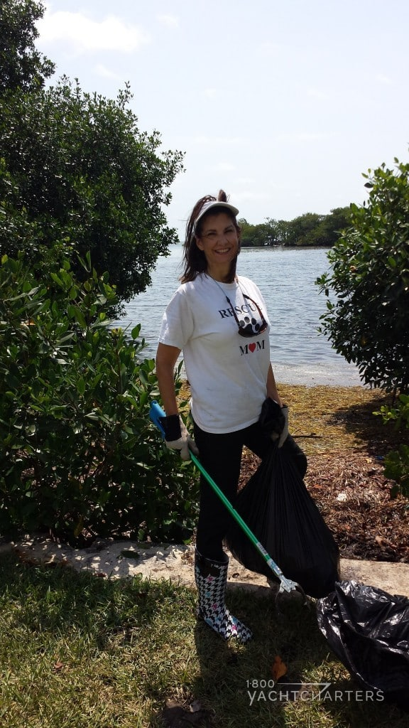 Jana Sheeder, President of 1-800 Yacht Charters poses with garbage bag during bay cleanup
