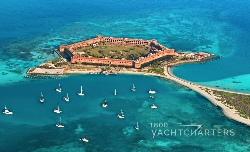 dry tortugas national park off of key west florida - a fort surrounded by ocean with multiple yachts anchored around one side of it