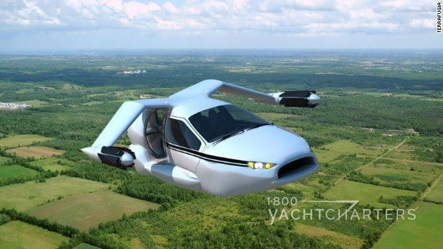flying hybrid car terrafugia tf-x flying over green trees and grass - blue sky in background