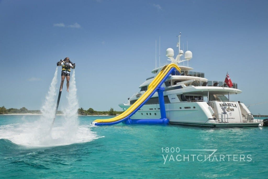 Back of yacht with inflatable slide set up and person flying over the water with a backpack like James Bond wore in the movie Thunderball