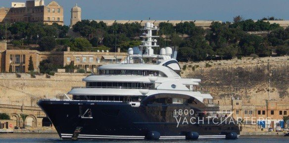 largest yacht charter vessel Serene in Malta - blue hull - white superstructure - rocky background - dock in foreground