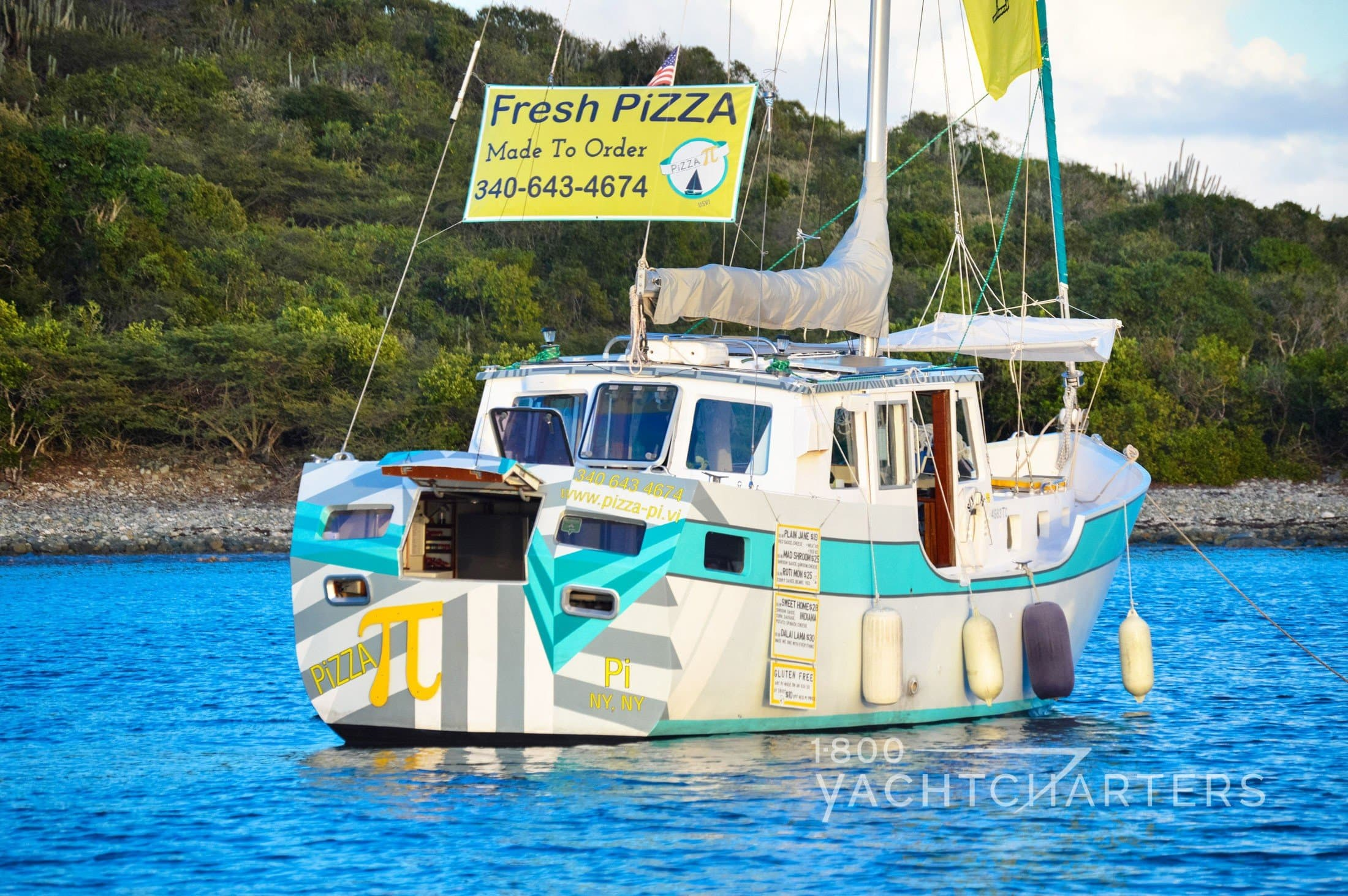 Pizza pi teal and white pizza sailboat anchored in St. Thomas USVI - advertisement for pizza on yellow sign hanging from sail lines