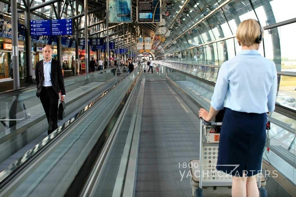 Man in suit - standing - and woman with basket - going opposite directions on moving conveyor belt in airport