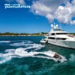 Photograph of motoryacht W at anchor. The yacht is facing the right side of the photo. Someone is riding a jetski next to the yacht, headed to the right, also