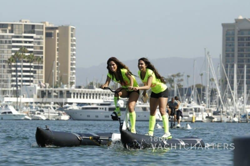 Two girls pedaling water bikes in a marina