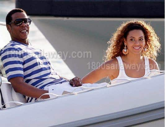 Photograph of Jay Z and Beyonce on a boat. Jay Z is seating at the back, and Beyonce is in front of him. He is wearing a blue and white horizontally striped shirt with white pants. She is wearing a white tank top and dangling earrings. They are looking at the camera and smiling. They are both seated