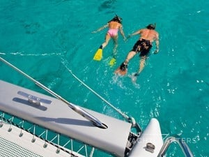 2 people snorkeling next to a sailboat
