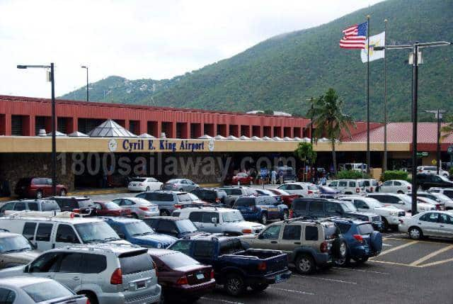 Photo of the Cyril E. King airport in St. Thomas, USVI.. The photo is taken from the parking lot toward the main building. There is a beautiful green mountain in the background.