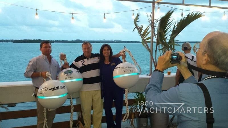 Jana Sheeder poses with Guy Harvey representative. Both hold mooring reef buoys that are placed above reefs in the ocean to protect reefs from anchor damage from boats. The round buoys reflect a horizontal line in the photo, as the photographer flash hits them. Best karma for generosity in yacht charters