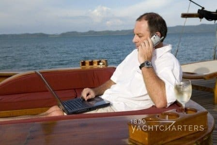 man on wooden boat talking on cellphone